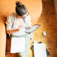 Young woman studying sitting on the floor