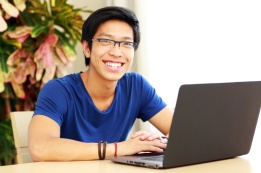 Cheerful young man sitting at the table with laptop